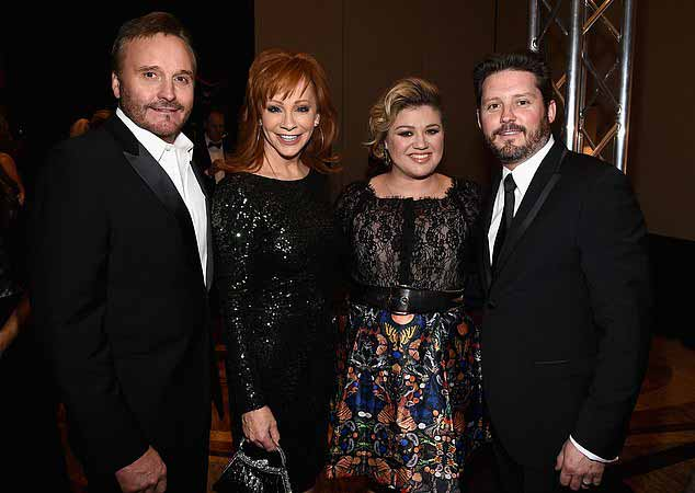 Different rule book: Blackstock and father Narvel's lawyers say they are not subject to California's Talent Agencies Act and that if they were a one-year statue of limitations would curb how much restitution Kelly could recoup. Above Narval, Kelly, and Brandon are seen with the elder Blackstock's ex-wife Reba McEntire