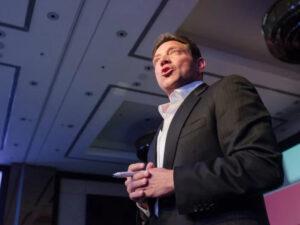 Jordan Belfort speaking to a crowd and wearing a black suit. (credit: seeshooteatrepeat / Shutterstock.com)